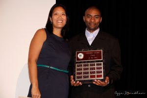 Div.2 Men's Basketball Coach Rowan Barnes accepts the award from Mai-Anh Nguyen, Athletics Coordinator