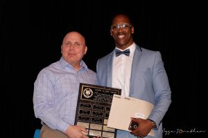 Brian Harelimana (right) accepts the Football Alumni Award from Coach Peter Chryssomalis